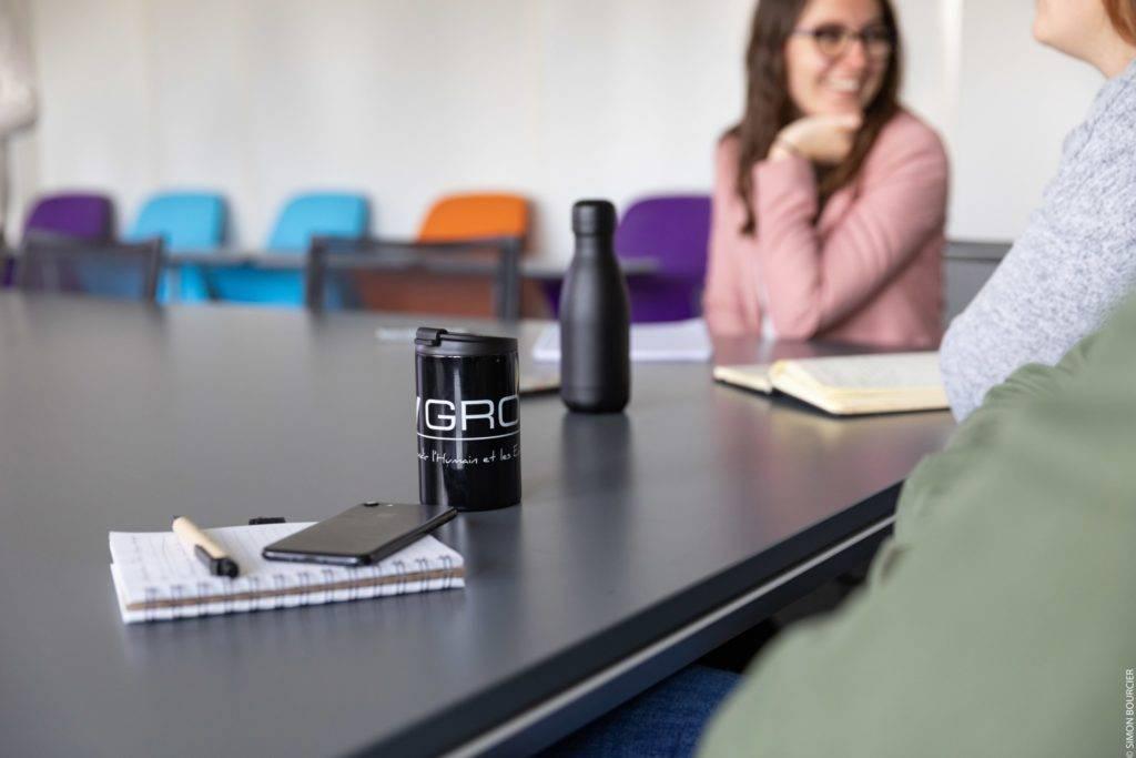 Gros plan sur cahier, crayon, téléphone et tasse MV Group, collaboratrice en fond