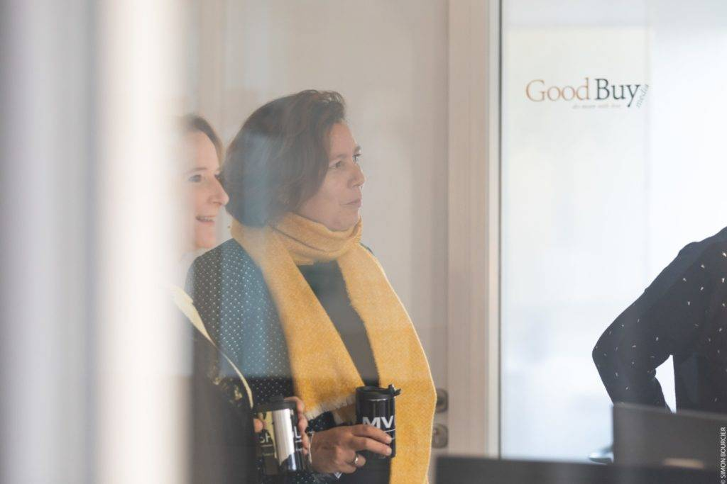 Collaboratrices devant une vitre avec logo GoodBuy media