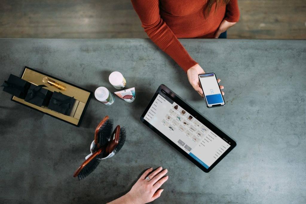 Clientes payant avec son téléphone devant un écran - Photo Blake Wisz